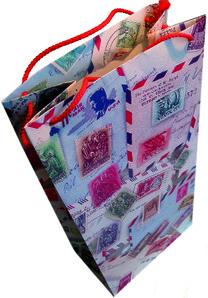 Geschenktasche mit Reisemotiven wie Postkarten und Briefmarken